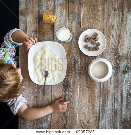 child near table having a meal with semolina