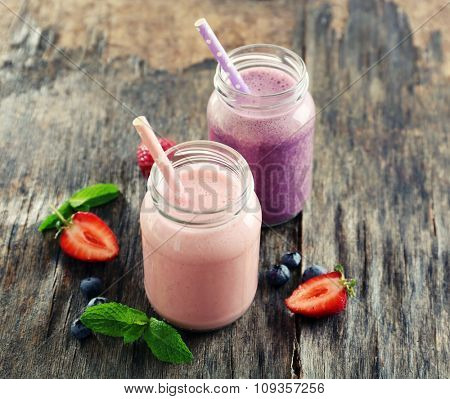 Healthy strawberry yogurt with mint and berries around on wooden background