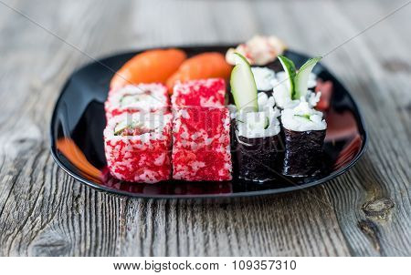 assorted Japanese sushi on a plate with chopsticks on wooden table