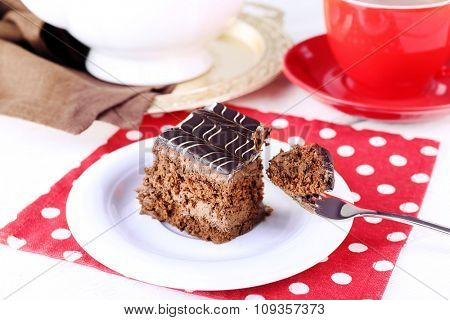 Served table with chocolate cakes and a cup of tea on red dotted background