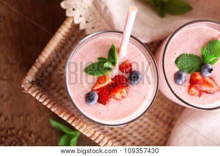 Fresh strawberry yogurt on wicker tray on wooden background