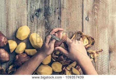 hands peeling potato on wooden board