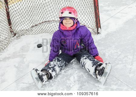 child on the hockey ice with a puck.