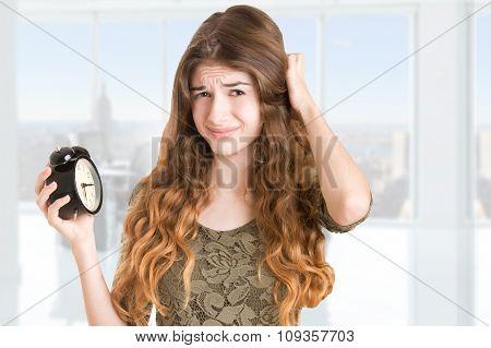 Woman Looking At An Alarm Clock