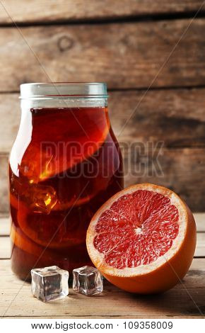 Iced tea with grapefruit on wooden background