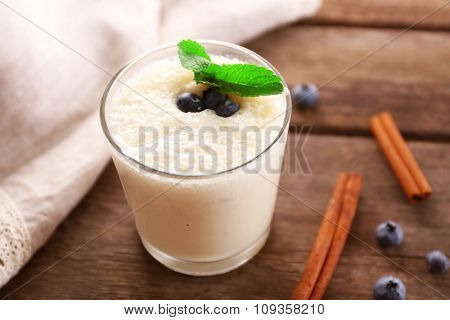 Fresh yogurt decorated with blueberries and cinnamon against wooden background