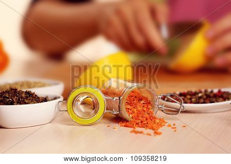 Dried carrots in the jar and variety of spices on the kitchen table
