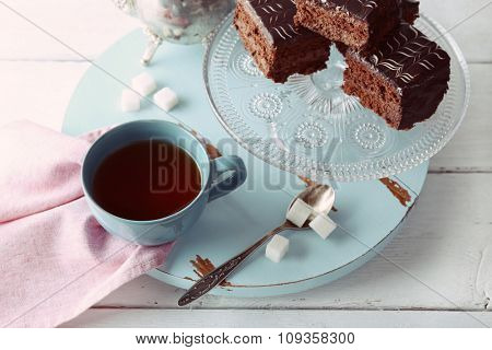 Served table with a teapot, a cup of tea and chocolate cakes on blue and whit background close-up