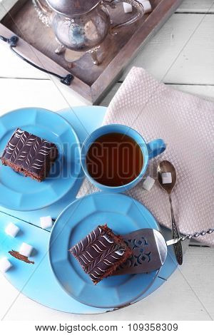 Served table with a cup of tea and chocolate cakes on blue plates close-up