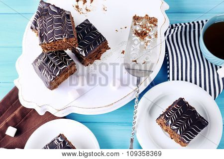 Served table with a cup of tea and chocolate cakes on white plates close-up