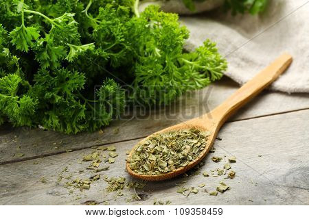 Fresh and dries parsley on wooden background