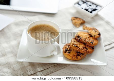 Cup of coffee and tasty cookies with chocolate crumbs on grey checkered napkin, close up