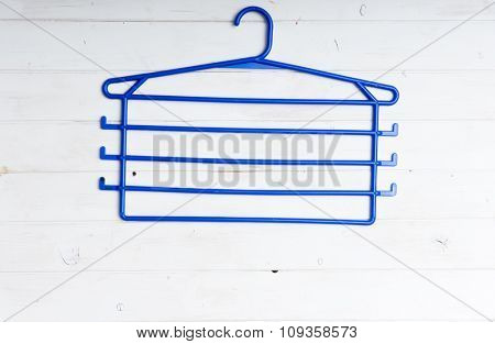 blue plastic clothes hanger on white wooden background