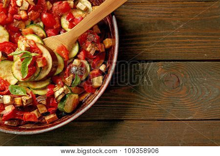 Tasty vegetarian ratatouille made of eggplants, squash, tomatoes and onions in black cast iron pan, on wooden table background