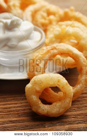Chips rings with white sauce on plate on wooden background