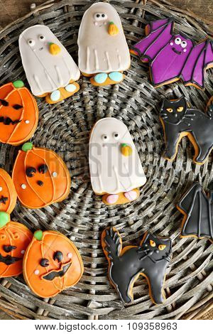 Creative cookies for Halloween party on wicker plate