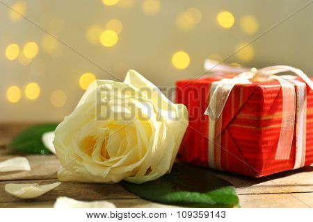A gift in the box and a white rose, on blurred background