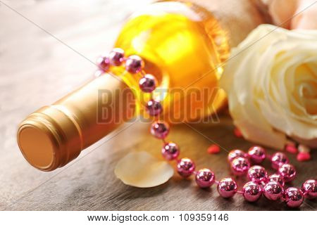 A bottle of wine, bead and a white rose on wooden background, close-up