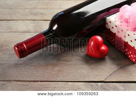 A bottle of wine and a gift in the box, on wooden background