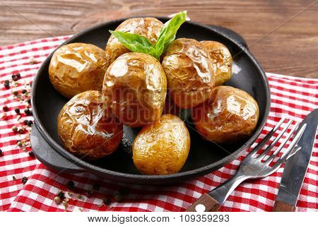 Baked potatoes in pan on checkered napkin on wooden table, closeup