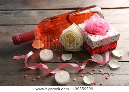 A bottle of wine, candles, a white rose and a gift in the box, on wooden background