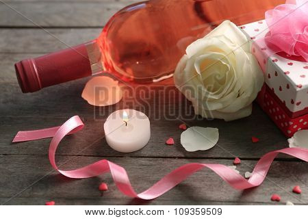 A bottle of wine, a candle, a white rose and a gift in the box, on wooden background