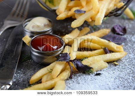 French fries with sauce and tableware on table, close-up