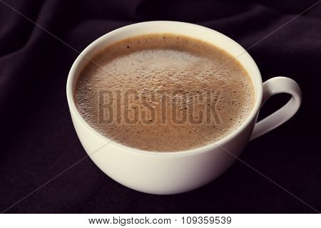 Cup of coffee and sugar on black tablecloth closeup