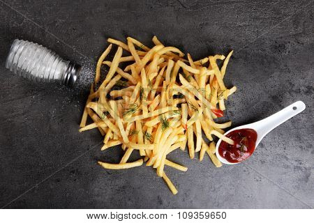 french fries with ketchup, salt and dill on table