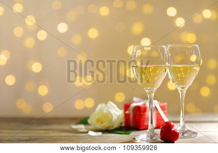 Glasses of wine, white roses and a gift in the box, on blurred background