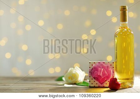Setting of a bottle of wine, a gift in the box and other decoration, on blurred background