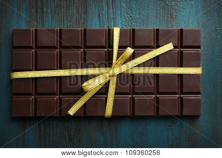 Dark chocolate bar with colorful bow on color wooden background