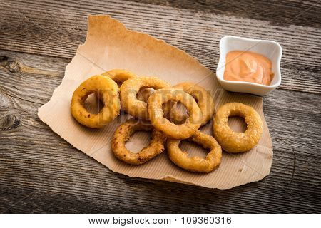 fried onion rings on parchment with sauce on a wooden background