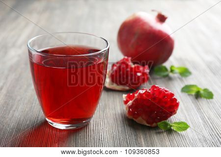 A glass of tasty juice and garnet fruit, on wooden background