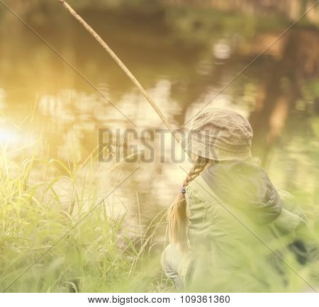 little fisher girl holds a rod sitting near a river