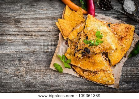 quesadilla with spices and vegetables on a wooden background