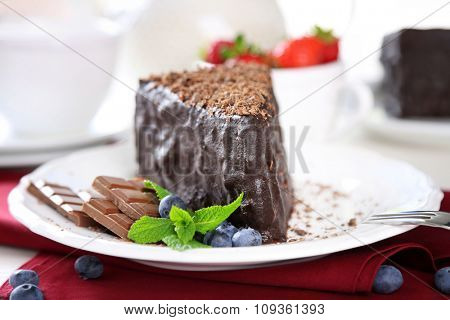 Chocolate cake with chocolate cream on plate, on light background