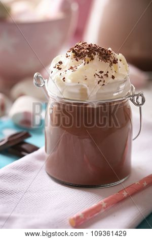 Glass jar of chocolate milk on table close-up