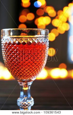 A glass of pink wine on blurred lighted background
