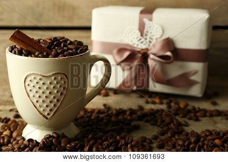 Beautiful gift with bow and coffee grains in mug, on wooden background