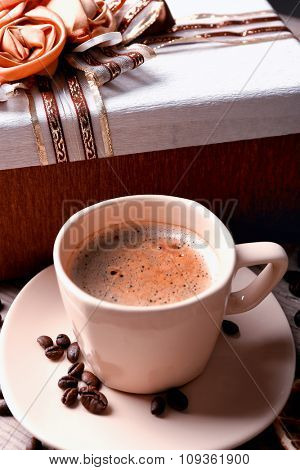 Beautiful gift, cup with coffee and coffee grains on wooden background