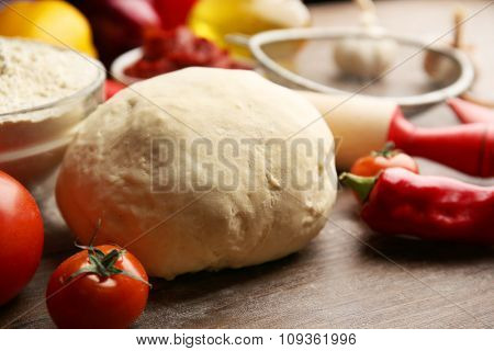 Dough balls and ingredients for pizza, on the table
