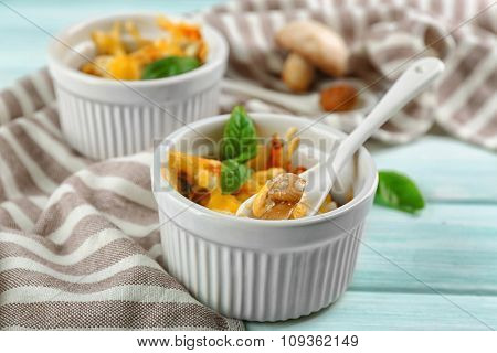 French dish julienne. Mushroom, chicken and cheese gratin in ceramic bowls, on wooden background