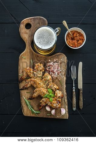 Fried chicken wings on rustic serving board, spicy tomato sauce, herbs and mug of light beer over bl