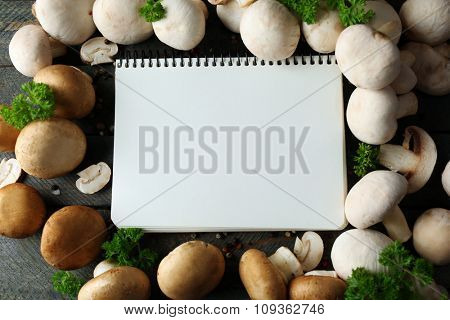 Fresh mushrooms and empty notebook on wooden background