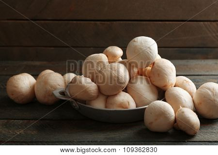Mushrooms in bowl on wooden surface