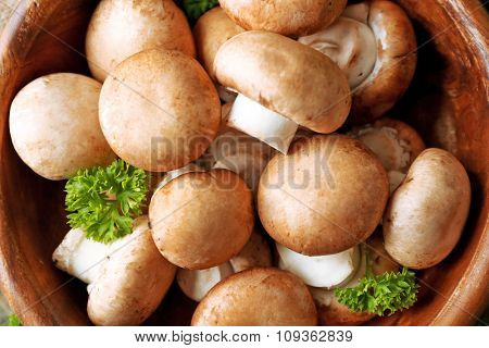 Mushrooms in wooden bowl, close-up