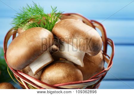 Mushrooms in basket on color wooden surface