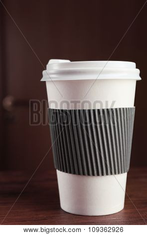 Paper cup of coffee on table, on wooden background