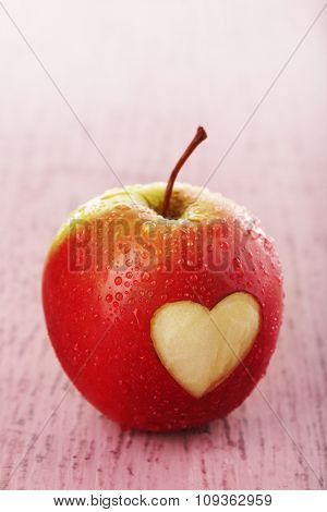 Apple with heart on wooden table